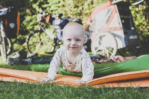 Portrait of happy baby with camping mat in grass - IHF00093