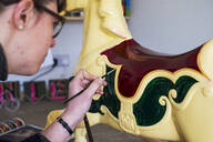 Close up of woman in workshop, painting traditional wooden carousel horse from merry-go-round. - MINF11577
