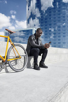 Man with yellow bicycle sitting on stairs, using smartphone, Barcelona, Spain - JND00056