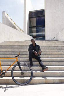 Man taking a selfie, sitting on step next to his bike - JND00071