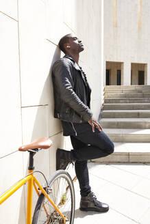 Man standing next to his bike, wireless earphones - JND00074