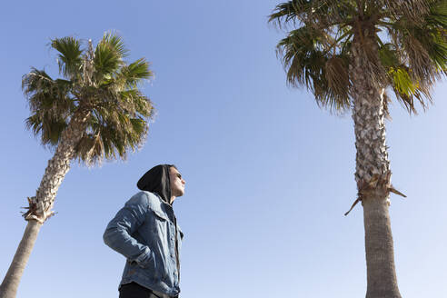 Young man standing among palm trees against blue sky - JPTF00132