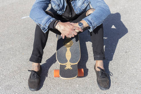 Tattooed young man sitting on longboard, partial view - JPTF00135