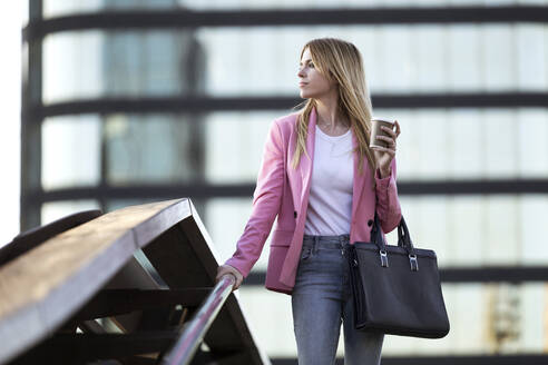 Young businesswoman using smartphone and holding coffee to go - JSRF00192