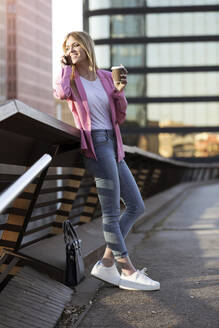 Young businesswoman using smartphone and holding coffee to go - JSRF00195