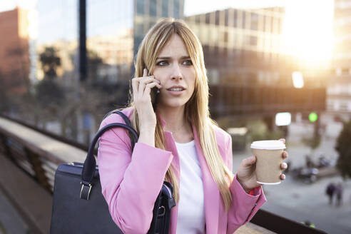 Young businesswoman using smartphone and holding coffee to go - JSRF00201