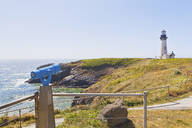 Telescope overlooking lighthouse on cliff, Newport, Oregon, United States - MINF11705