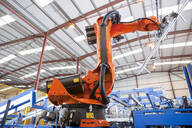 Robotic machinery lifting steel fencing on production line in manufacturing plant - JUIF01342