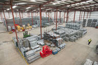Workers walking through warehouse with steel tubing and finished safety barriers - JUIF01345