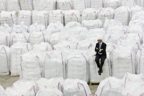 Businessman sitting on top of large bags of recycled plastic pellets in warehouse - JUIF01351