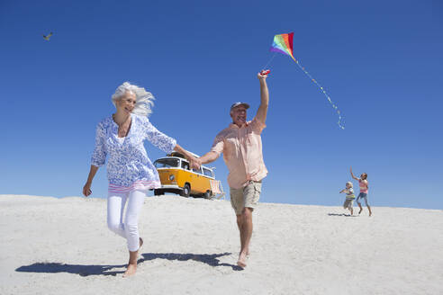 Grandparents and grandchildren running with kite on sunny beach with van in background - JUIF01354