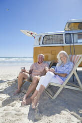 Portrait of smiling senior couple sitting on lounge chairs on sunny beach near van - JUIF01357