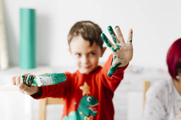 Boy showing a brush in one hand and the other painted green while doing crafts at home - JRFF03242