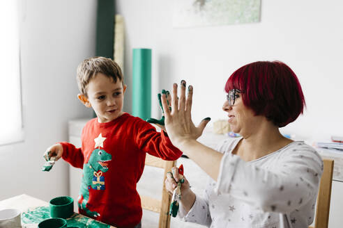 Happy mother and son high five while doing crafts at home - JRFF03248