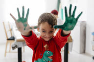Boy showing his hands painted green while doing crafts at home - JRFF03251