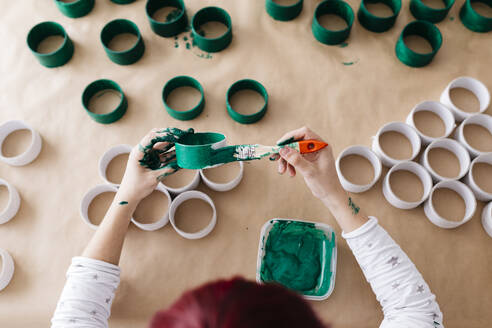 Top view of woman's hands painting a roll of cardboard with a green brush - JRFF03254