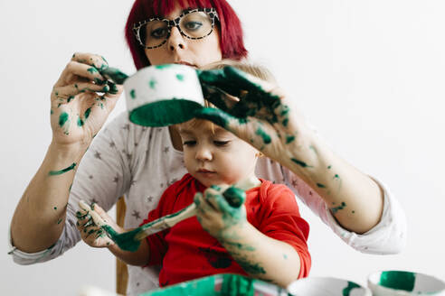 Mother and daughter doing crafts at home, painting cardboard rolls to make a Christmas tree. - JRFF03260