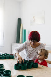 Mother and daughter doing crafts at home, with cardboard rolls to make a Christmas tree - JRFF03263