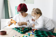 Mother and daughter doing crafts at home with accessories to make a Christmas tree - JRFF03266