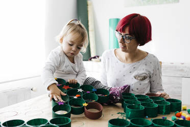 Mother and daughter doing crafts at home with accessories to make a Christmas tree - JRFF03269