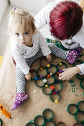 Top view of mother and daughter doing crafts at home with accessories to make a Christmas tree - JRFF03272