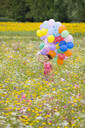 Smiling girl running with bunch of balloons among wildflowers in sunny meadow - JUIF01364