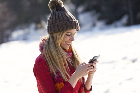 Young blond woman using smartphone in winter - JSRF00229