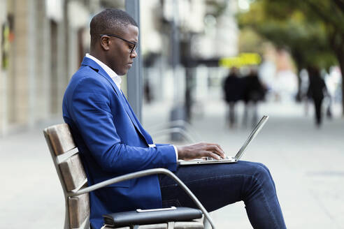 Young businessman wearing blue suit jacket sitting on bench and using laptop - JSRF00235