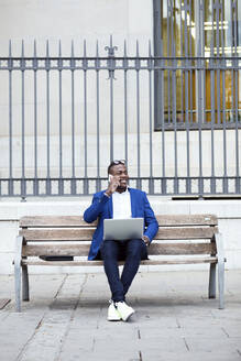 Young businessman wearing blue suit jacket sitting on bench and using smartphone - JSRF00238