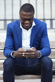 Young businessman wearing blue suit jacket sitting on bench and using smartphone - JSRF00241
