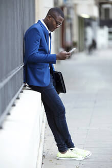 Young businessman wearing blue suit jacket and using smartphone - JSRF00250