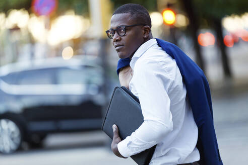 Young businessman with blue suit jacket over his shoulder and laptop bag - JSRF00253