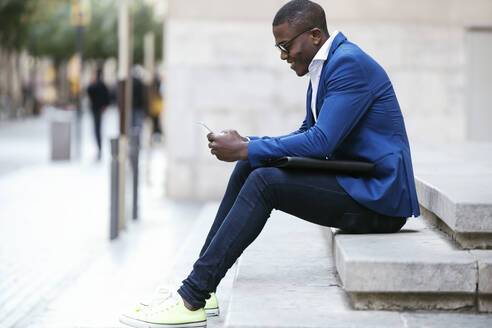Young businessman wearing blue suit jacket, sitting on step and using smartphone - JSRF00259