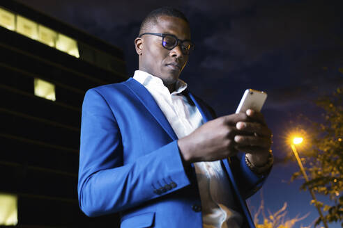 Young businessman wearing blue suit jacket and using smartphone at night - JSRF00268