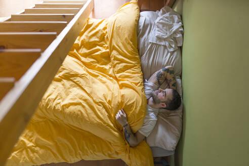 Tattooed man lying in bed, wooden ladder - JPTF00139