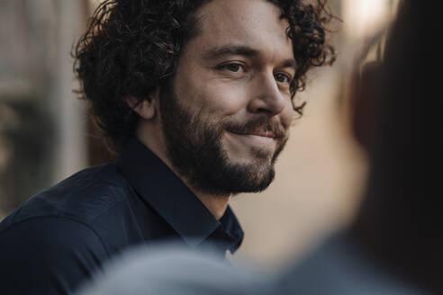 Smiling man talking to a friend - KNSF05997