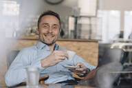 Successful businessman sitting in coffee shop, drinking coffee - KNSF06027