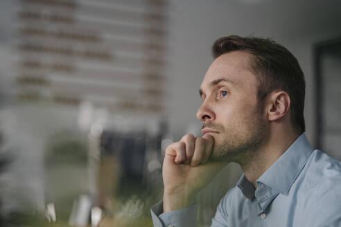 Successful businessman sitting in coffee shop, thinking - KNSF06042