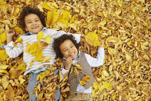 Mixed race boys laying in yellow autumn leaves - BLEF06755