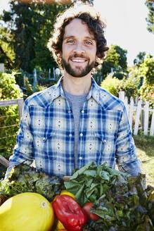 Caucasian man harvesting vegetables in garden - BLEF06788