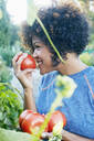 Mixed race woman smelling tomatoes in garden - BLEF06806