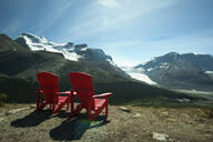 Red lawn chairs overlooking scenic mountain landscape - MINF12308