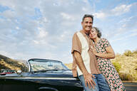 Couple smiling near classic convertible - BLEF06845