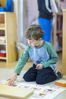 Boy arranging cards on floor in classroom - BLEF06914