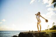 Woman standing on wall near ocean - BLEF06998
