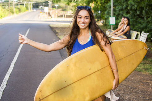 Pacific Islander surfer hitch hiking on rural road - BLEF07010