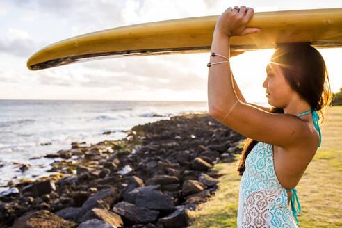 Pacific Islander surfer carrying surfboard on rocky beach - BLEF07013
