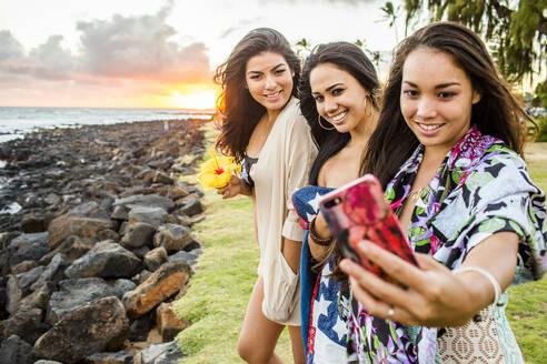 Pacific Islander women taking cell phone photograph near rocky beach - BLEF07016