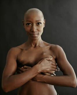 Nude African American cancer survivor covering her breasts - BLEF07025