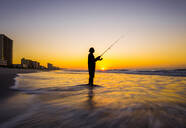 Blurred view of silhouette of man fishing in waves on beach at sunset - MINF12333